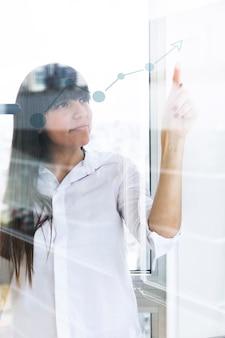 Jovem empresária apontando o dedo no gráfico crescente em vidro transparente