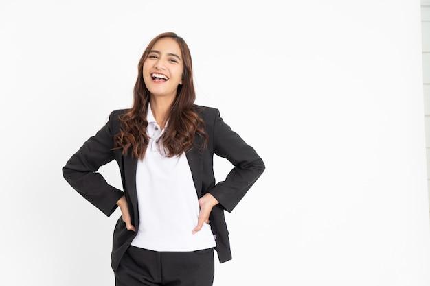 Jovem empresária asiática animada rindo alegremente com as duas mãos na cintura