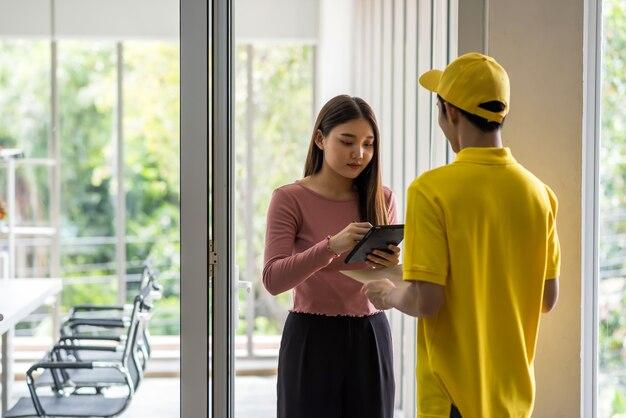 Jovem empresária asiática assinar assinatura no tablet digital antes de pegar o pacote do envelope na porta da sala de reuniões do escritório. entregador de correio postal