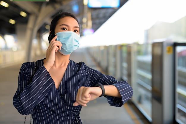 Jovem empresária asiática com máscara pensando enquanto fala ao telefone e verifica o smartwatch na estação