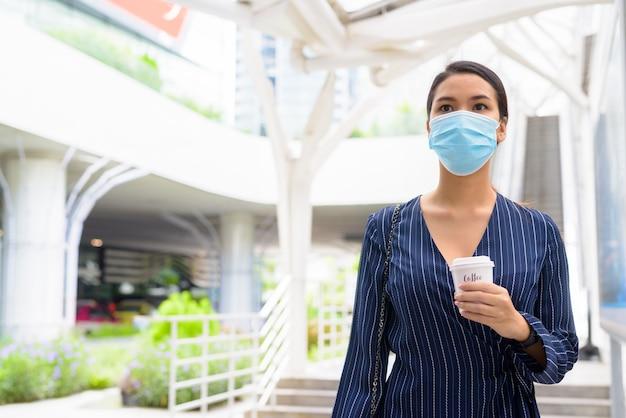 Jovem empresária asiática com máscara tomando café em qualquer lugar como o novo normal durante covid-19