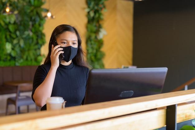 Jovem empresária asiática com máscara usando laptop e falando ao telefone dentro da cafeteria
