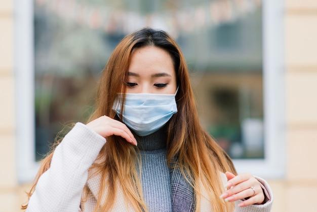 Jovem empresária asiática com máscara usando telefone e sentada à distância fora da cafeteria