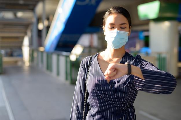 Jovem empresária asiática com máscara, verificando as horas ao sair da estação de trem
