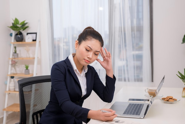 Jovem empresária asiática com olhos cansados e dor de cabeça
