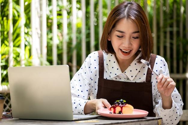 Jovem empresária asiática é dona de uma cafeteria, segurando um garfo e comendo bolo de frutas vermelhas