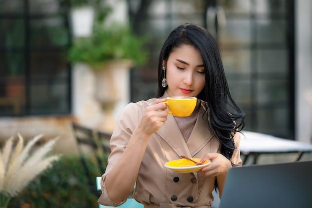 Jovem empresária asiática e freelance sentada na mesa de madeira