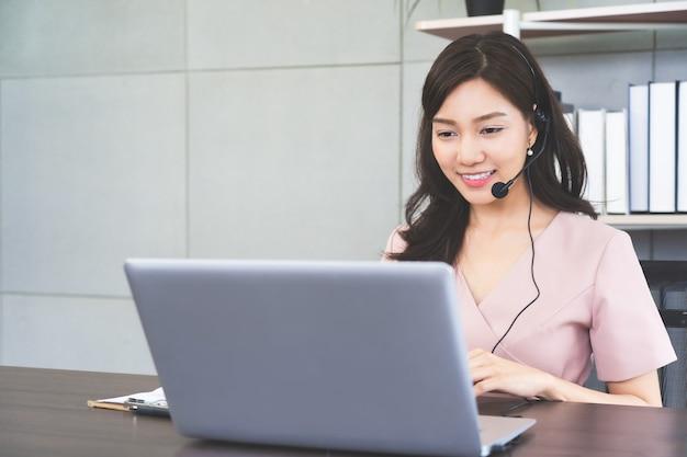 Jovem empresária asiática em fones de ouvido com computador em reunião de conferência vdo online