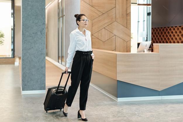 Jovem empresária asiática em trajes formais puxando a mala enquanto espera pela recepcionista no saguão do hotel