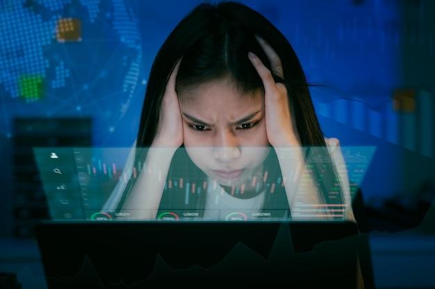 Jovem empresária asiática está com dor de cabeça. comerciante procurando computador tem problemas financeiros com gráficos no escritório à noite.