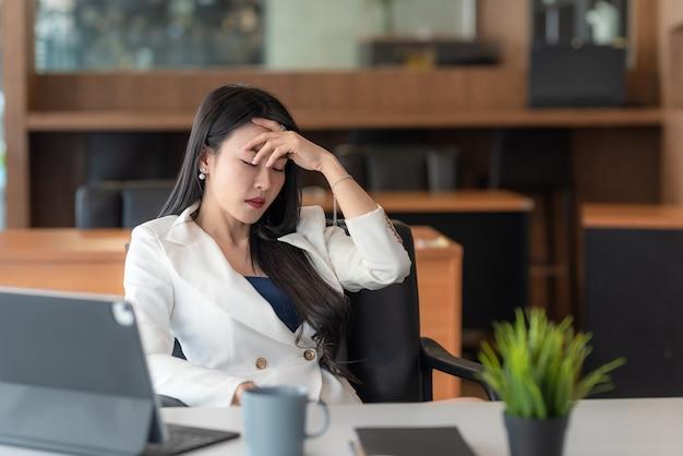 Jovem empresária asiática está entediada com o estresse de trabalhar no escritório.