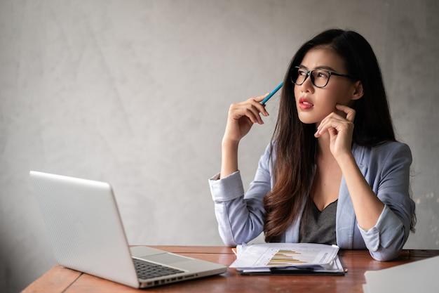 Jovem empresária asiática feliz de camisa azul, trabalhando em casa, usando um laptop e pensando em uma ideia para o seu negócio