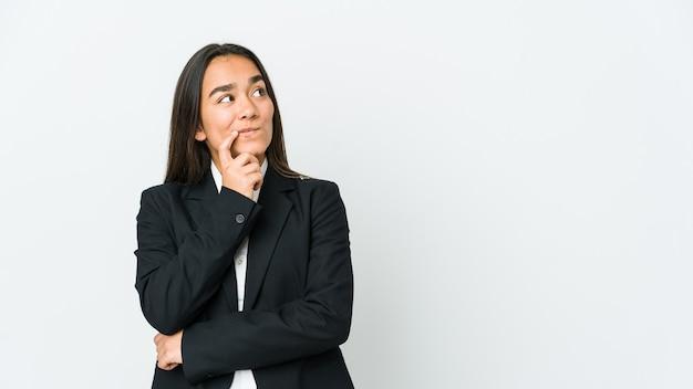 Jovem empresária asiática isolada na parede branca, olhando de soslaio com expressão duvidosa e cética.