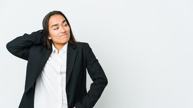 Jovem empresária asiática isolada na parede branca, tocando a parte de trás da cabeça, pensando e fazendo uma escolha.