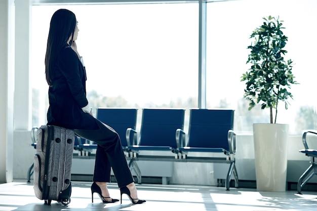 Jovem empresária asiática no aeroporto com carrinho