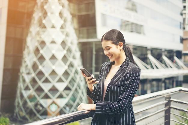 Jovem empresária asiática que usa no smartphone móvel. profissional jovem feminina na cidade em frente ao grande prédio.