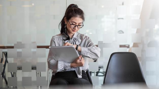 Jovem empresária asiática segurando uma carteira olha para o relógio e aguarda uma entrevista de emprego no escritório.