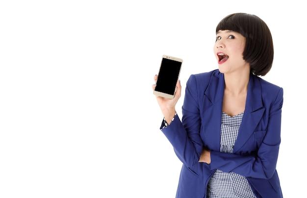 Jovem empresária asiática sorridente com roupa elegante, mostrando um celular moderno com tela preta vazia sobre fundo branco