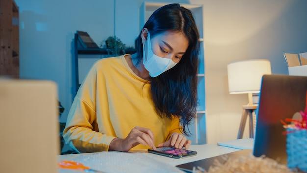 Jovem empresária asiática usando máscara facial, verificando o pedido de compra no smartphone
