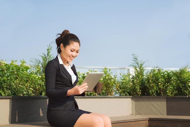 Jovem empresária atraente de retrato trabalhando com tablet digital.