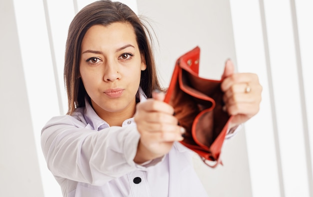 Jovem empresária atraente mostrando uma carteira vazia para a câmera.