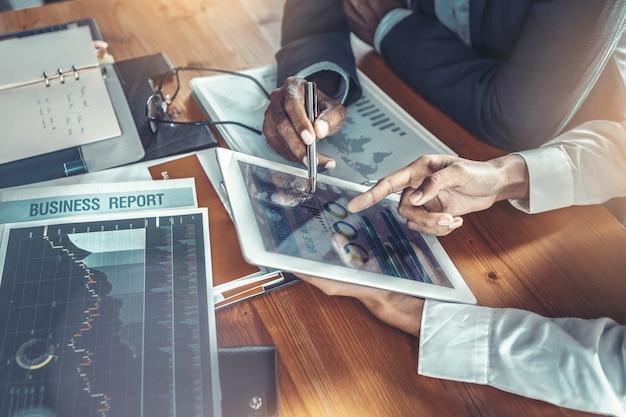 Jovem empresária atraente trabalhando com touch pad foi orientada e consultada pelo colega sênior.