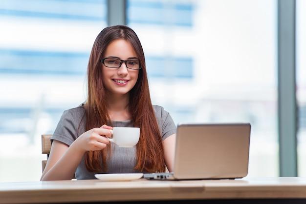 Jovem empresária bebendo chá no escritório