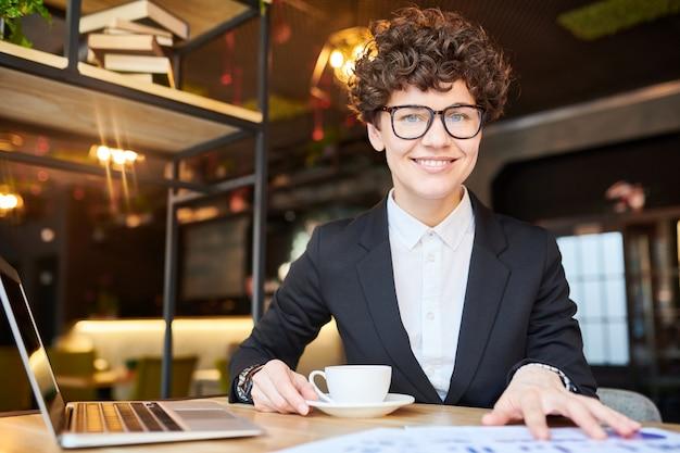 Jovem empresária bem-sucedida em trajes formais e óculos, sentado na frente da câmera enquanto trabalhava e tomando chá