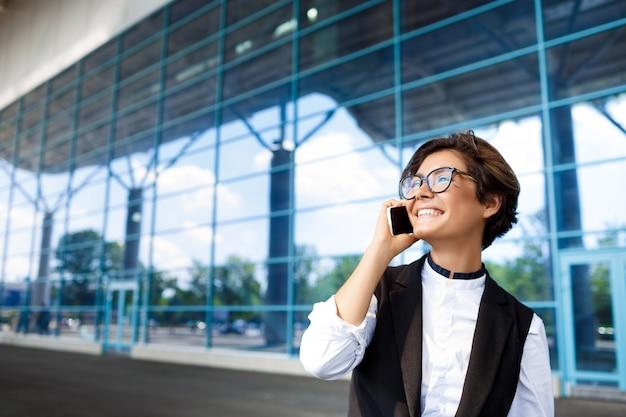 Jovem empresária bem-sucedida, falando no telefone, em pé perto do centro de negócios.