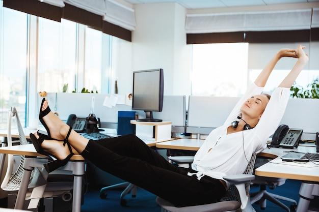 Jovem empresária bem sucedida linda descansando, relaxando no local de trabalho, escritório