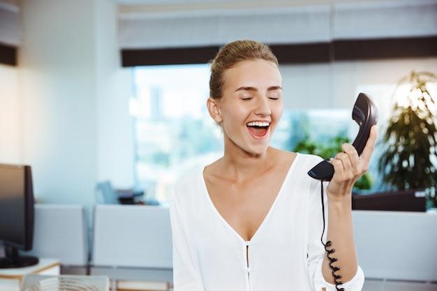 Jovem empresária bem sucedida linda sorrindo, falando no telefone, escritório