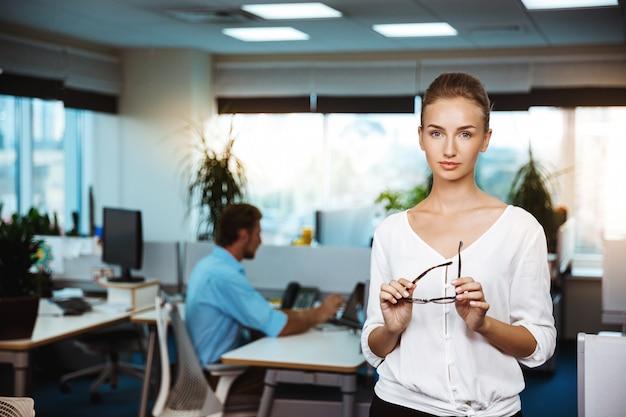 Jovem empresária bem sucedida linda sorrindo, posando, escritório