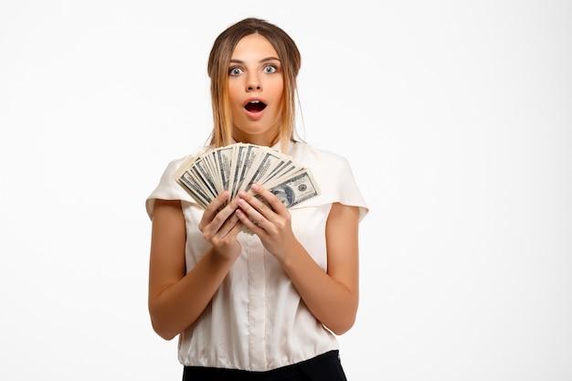 Jovem empresária bem-sucedida, segurando o dinheiro sobre fundo branco.
