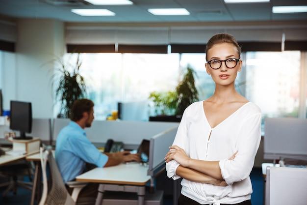 Jovem empresária bem-sucedida, sorrindo, posando com os braços cruzados, sobre o escritório