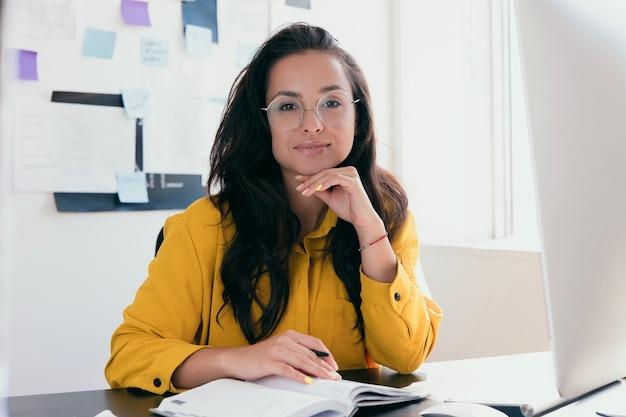 Jovem empresária bem-sucedida trabalhando em casa ou no escritório