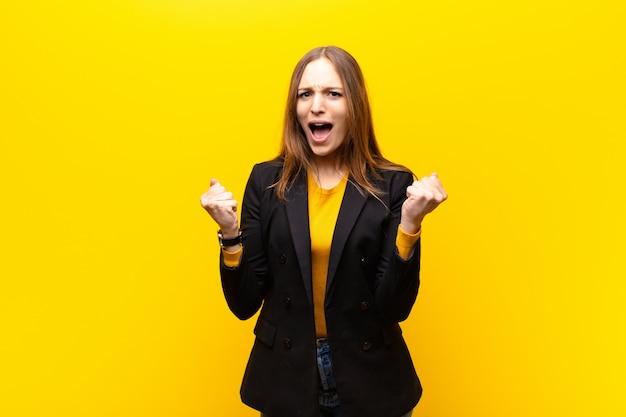 Jovem empresária bonita gritando agressivamente com uma expressão de raiva ou com os punhos cerrados comemorando sucesso contra fundo laranja