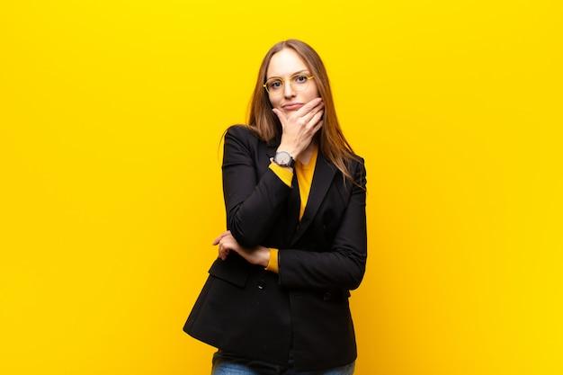 Jovem empresária bonita olhando séria, pensativa e desconfiada, com um braço cruzado e mão no queixo, opções de ponderação contra a parede laranja