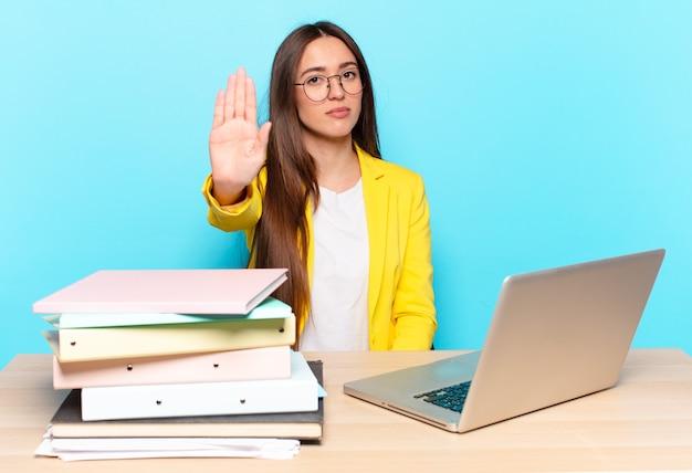 Jovem empresária bonita parecendo séria, severa, descontente e irritada mostrando a palma da mão aberta fazendo gesto de pare