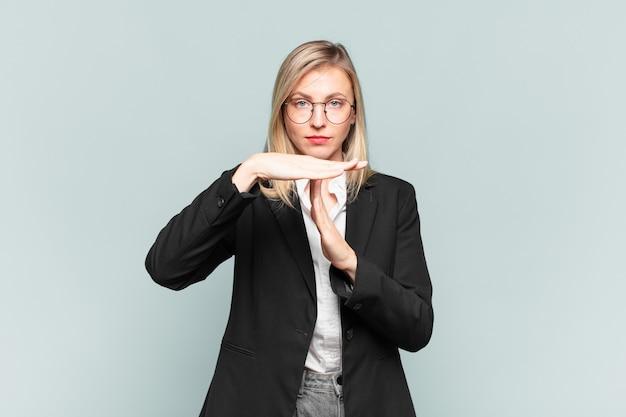 Jovem empresária bonita parecendo séria, severa, irritada e descontente, fazendo sinal de tempo limite