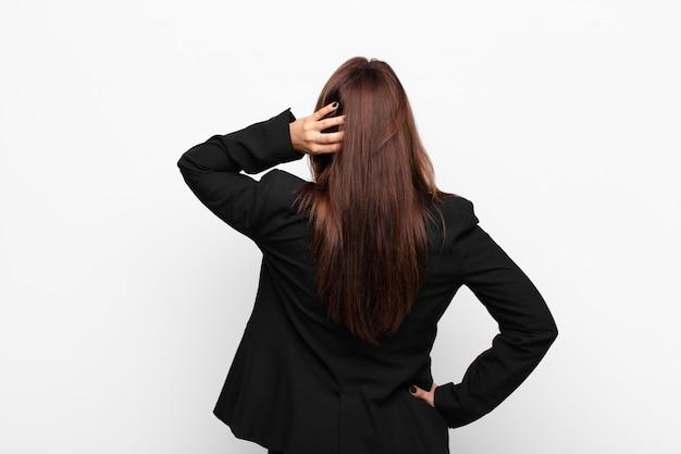 Jovem empresária bonita pensando ou duvidando, coçando a cabeça, sentindo-se confuso e confuso, vista traseira ou traseira contra parede branca