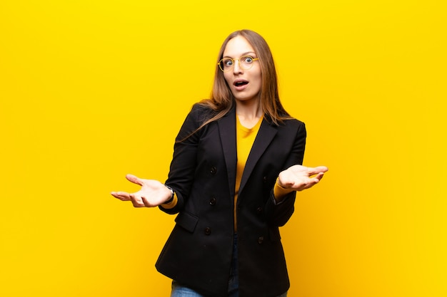 Jovem empresária bonita se sentindo extremamente chocada e surpresa, ansiosa e em pânico, com um olhar estressado e horrorizado contra a parede laranja