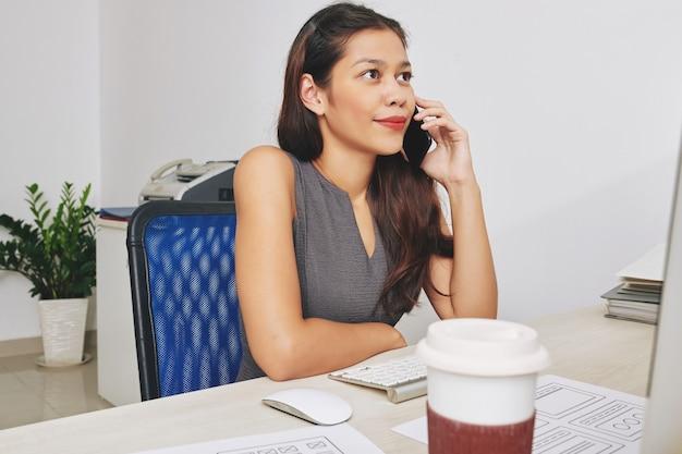 Jovem empresária bonita sorridente, sentada na mesa do escritório e falando ao telefone com um colega
