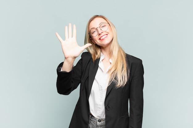 Jovem empresária bonita sorrindo e parecendo amigável, mostrando o número cinco ou quinto com a mão para a frente, em contagem regressiva