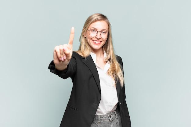 Jovem empresária bonita sorrindo e parecendo amigável, mostrando o número um ou primeiro com a mão para a frente, em contagem regressiva