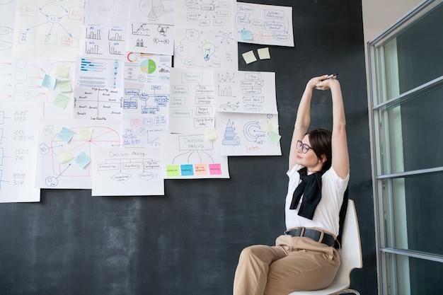Jovem empresária cansada esticando os braços enquanto está sentada na cadeira perto do quadro-negro e aproveitando uma pequena pausa