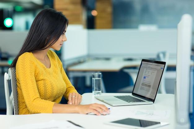 Jovem empresária casual usando laptop no escritório