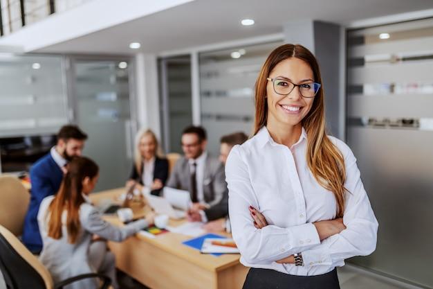 Jovem empresária caucasiana atraente com roupa formal em pé na sala de reuniões com as mãos cruzadas e olhando para a câmera. no fundo estão seus colegas trabalhando no projeto.