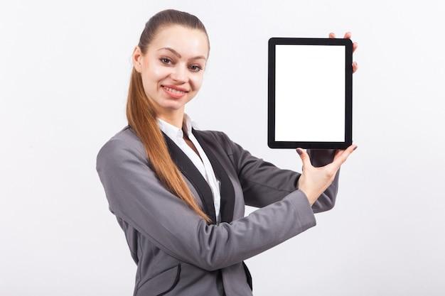 Jovem empresária caucasiana atraente no terno cinza segurar o tablet vazio