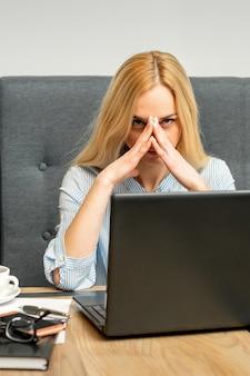 Jovem empresária caucasiana cansada do trabalho sentada à mesa de um café