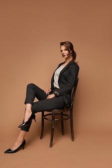Jovem empresária caucasiana confiante vestindo um terno cinza, sentada na cadeira na parede bege isolada com espaço de cópia